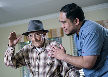 Resident waving with rehab staff member