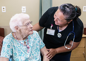 Nurse smiling with a resident while they are talking
