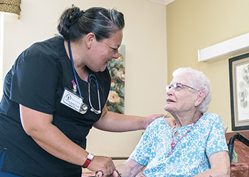Nurse holding the hand of a resident while they are talking