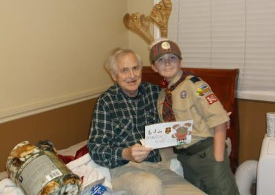 A boy scout giving a resident a gift.