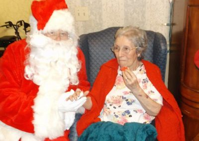 Santa holding a residents hand while she eats a cookie.