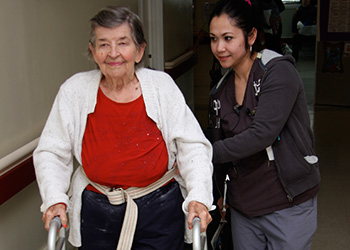 Nurse helping resident walk down the hall