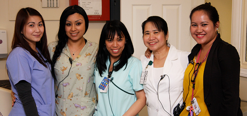 Nurses standing together smiling in the facility