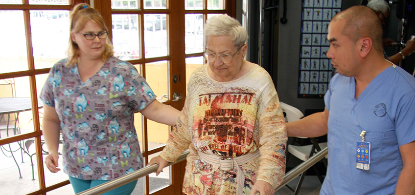 nurses helping resident walk during physical therapy