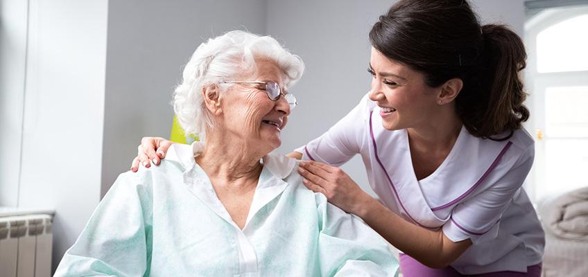 nurse talking to elderly women in wheelchair
