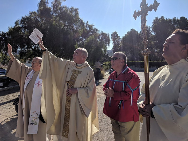 Monsignor Michael McKiernan, Pastor of Mission San Juan Capistrano and Basilica, and visiting Priest, Father Eamon O'Gorman of the Diocese of Orange, gather at the Old Mission Historic Cemetery entrance to formally bless our new entrance Crucifix. This special and unique handmade iron Crucifix was donated to us by the Blas Aguilar Adobe Foundation Board of Directors. Also pictured is Jerry Nieblas, President of the Capistrano Historical Alliance Committee and a Juaneno Band of Mission Indians and Juaneno descendant. Featured is Mass Cross Bearer, Wyatt Belardes. Wyatt has been the Cross Bearer and Altar Server at every Mass of Remembrance. Thank you, Wyatt.