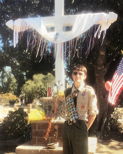 scout in front of a cross