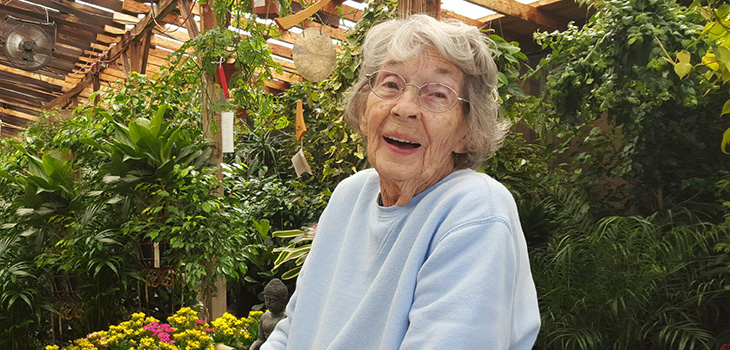 A resident in a greenhouse smiling with plants all around her, even hanging over head.