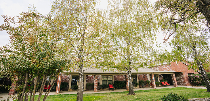 The community with brick walls and pilers with lush grass and mature trees in bloom out front.