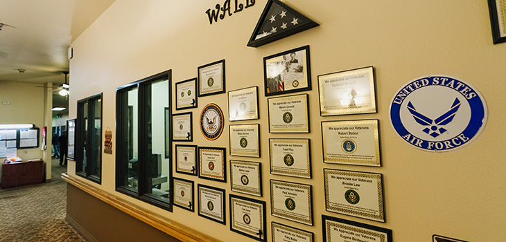 Wall of heroes with plaques on the wall and a flag in a glass case.