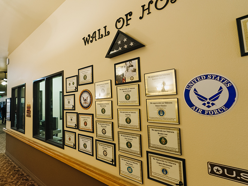 Wall of Hope with plaques on the wall and a framed American flag.