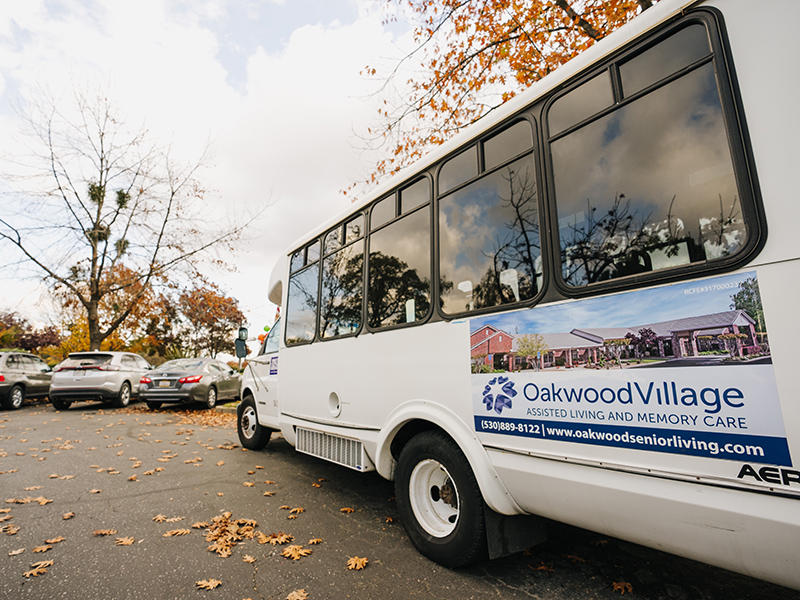 Oakwood Village bus parked in the parking lot with an Oakwood Village Assisted Living and Memory Care sign on the bus with the website and phone number.