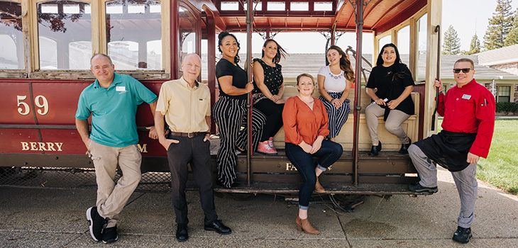 Staff members inside of an old caboose smiling together.