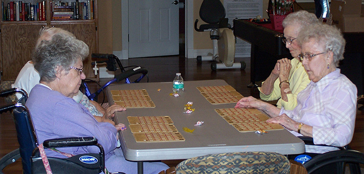 4 residents playing a game together at a table