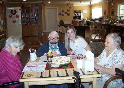 Residents coloring together with a staff member