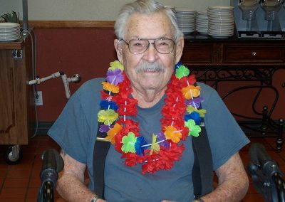 resident smiling and wearing a lei around his neck
