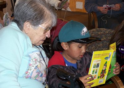 young visitor reading Curious George to a resident