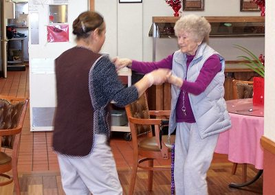 staff member and resident dancing together