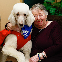 A resident smiling with a therapy dog.