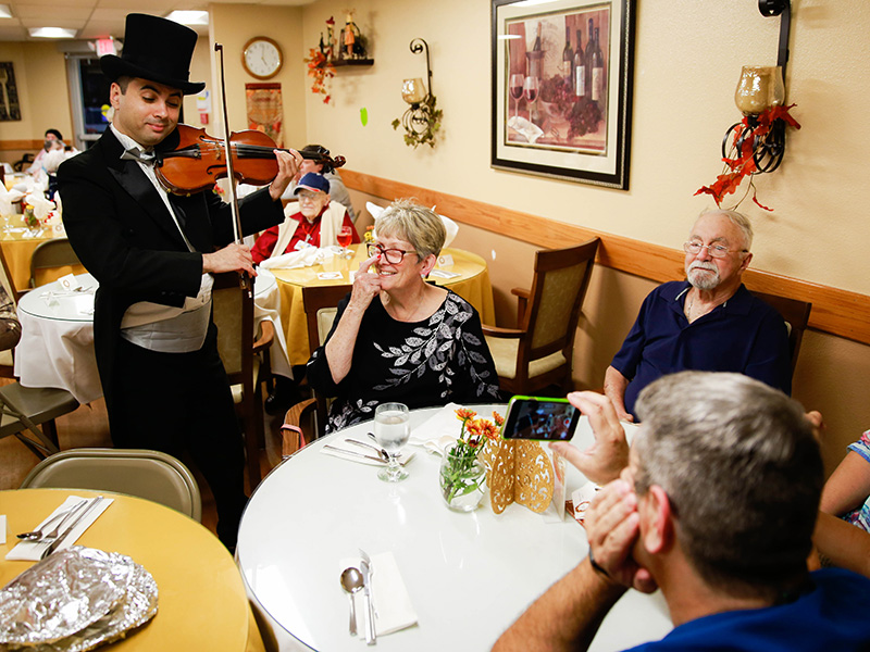 A violinist playing for residents eating.