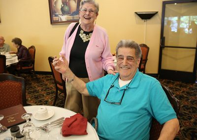 Two residents smiling together in the dining room