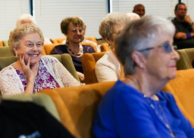 Residents smiling while listening to someone speak