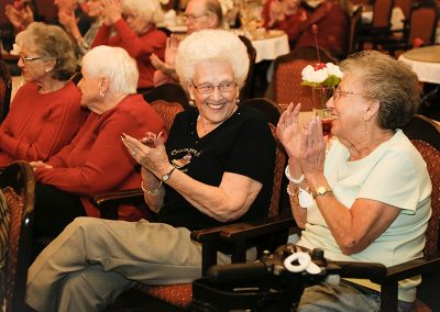 Residents laughing and clapping at a scheduled activity