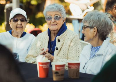Three residents enjoying some beverages outside