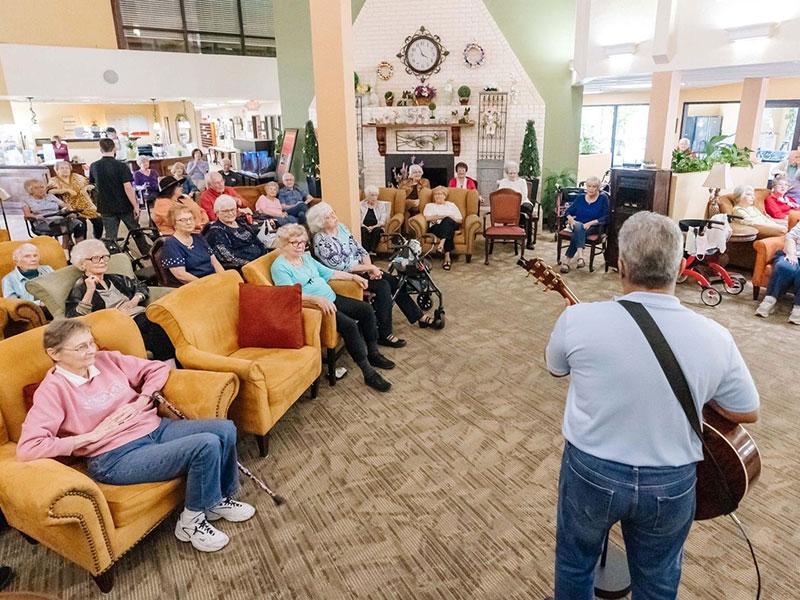 Sierra Regency residents listening to a guitar player
