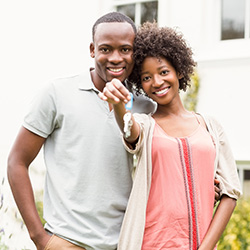 A man and a women hold up their keys to a new house, both smiling