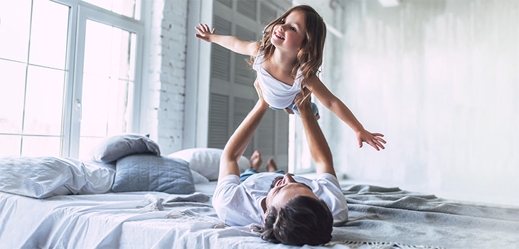Father holds up his daughter as she acts like plan flying in the sky while laying on a bed in their home
