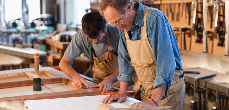 Two men measuring wood, they are building something