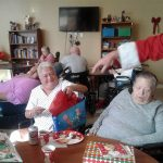 Residents opening gifts from Santa.