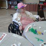 A resident wearing her decorated hat.