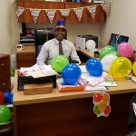 Administrator with Happy Birthday balloons all around him.