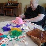 A resident customizing a cowboy hat.