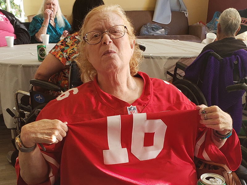 Resident holding up her number sixteen NFL jersey.