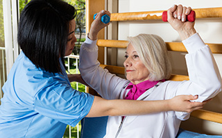 physical therapist helping resident with hand weights
