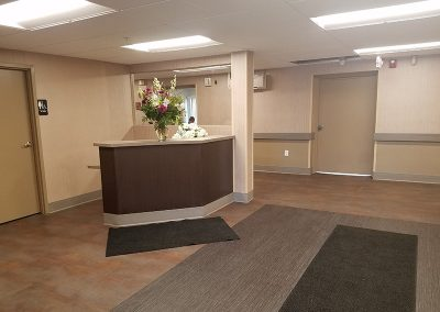 Lobby area with very clean floors and beautiful flowers on the counter