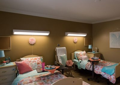 Female double occupancy room with flowers on the wall