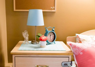 Female room with flowers on the end table and a glass angel