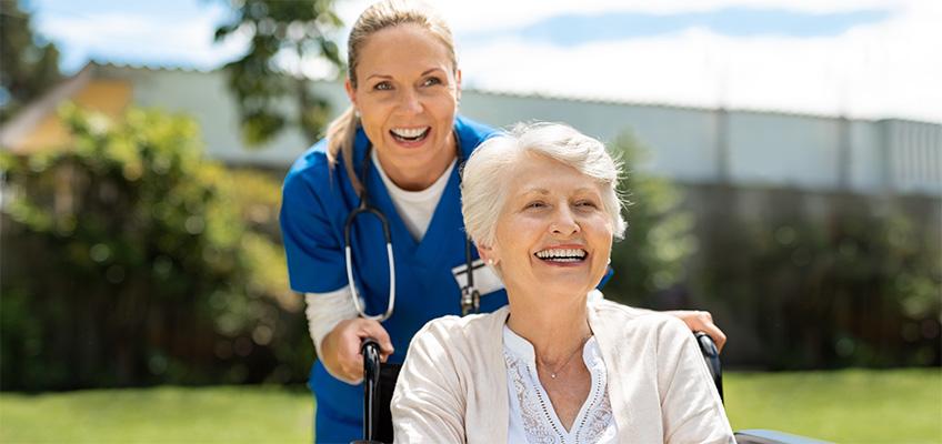 A nurse smiling with a senior in a wheelchair.