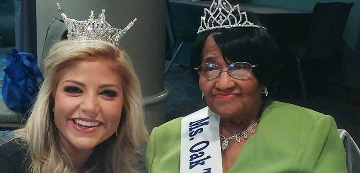 A resident and an employee both crowned with tiaras