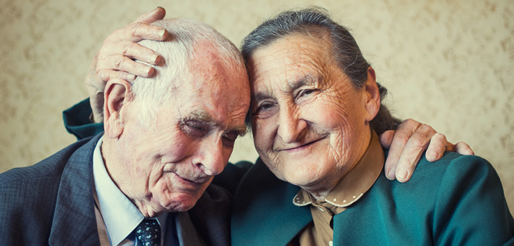 An elderly couple smiling and hugging