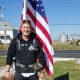 A veteran standing in front of a United States flag