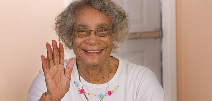 A woman smiling and waving her hand