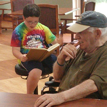 A boy reading his book to an older gentleman