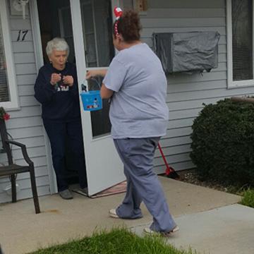 A woman giving an elderly woman a basket of treats