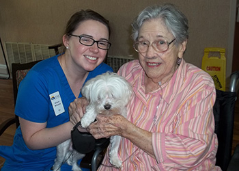 A nurse and a resident posing with a puppy