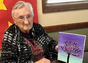A resident showing off her artwork